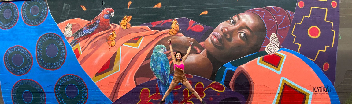 Artist Katherine Gailer jumping in front of Stark Place Mural in Sunshine